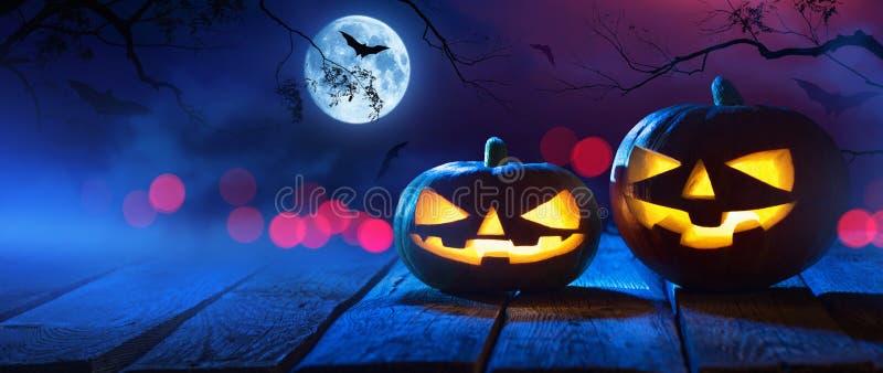 Halloween-Kürbise auf Holz in gespenstischen Forest At Night lizenzfreie stockbilder