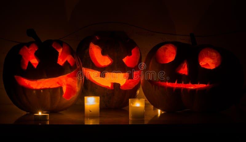 Halloween-Kürbise mit furchtsamem Gesicht und brennender Kerze stockbild