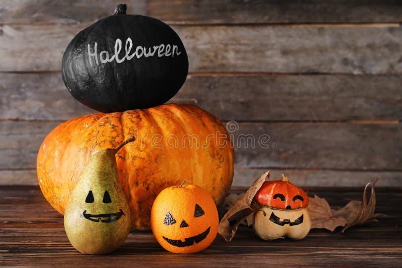 Halloween-Kürbise und gemalte Früchte auf hölzernem Hintergrund lizenzfreie stockbilder