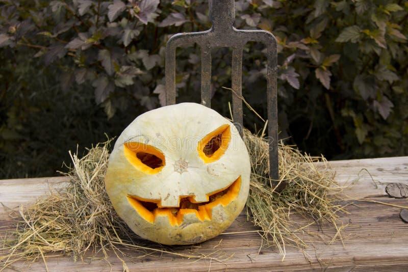 Halloween-Kürbissteckfassungslaterne auf einer Heugabel lizenzfreie stockfotos