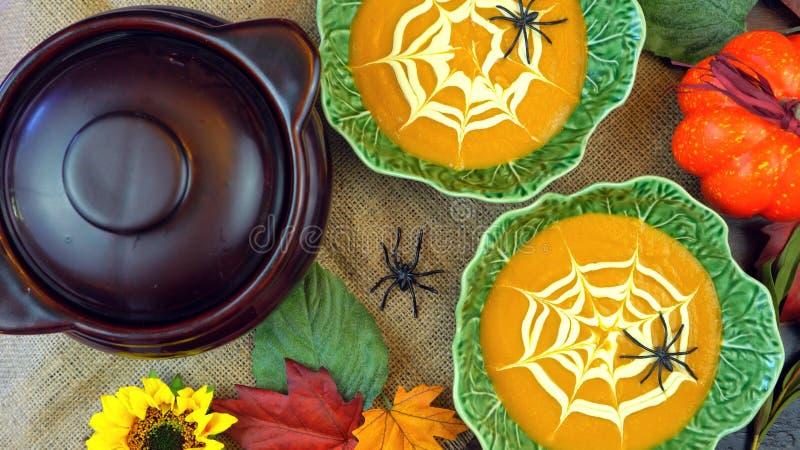 Halloween-Kürbissuppe mit Spinnennetz-Sauerrahmdekorationen lizenzfreie stockbilder
