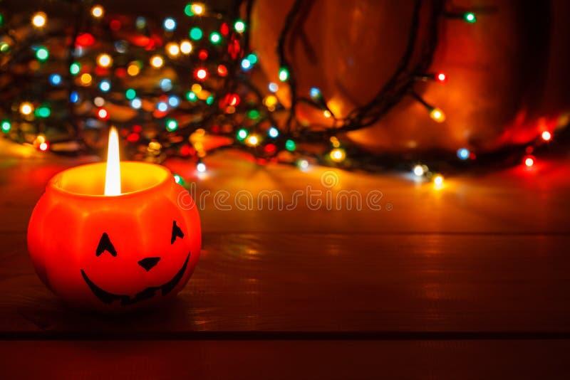 Halloween-Kerze in der Dunkelheit auf einem hölzernen Hintergrund Hinter dem Kürbis in den Lichtern der Girlande stockbilder