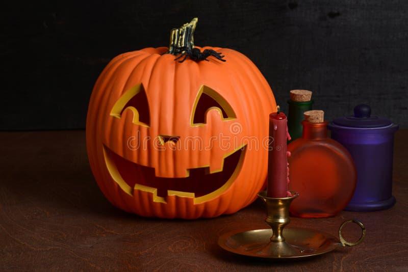 Halloween-Kerze mit Kürbis und Flaschen stockfotos