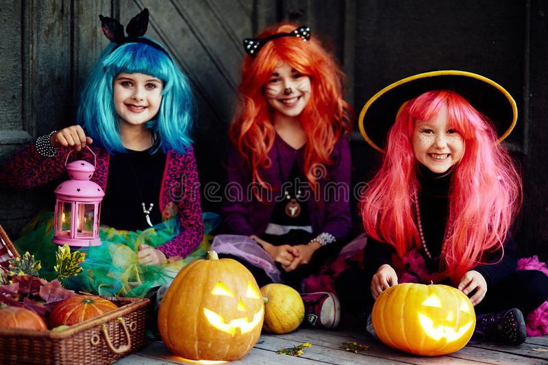 Halloween kids. Group of girls looking at camera on Halloween night surrounded by jack-o-lanterns royalty free stock images