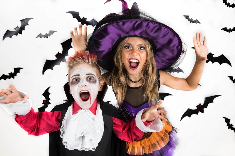 Halloween kids, Happy scary girl and boy dressed up in halloween costumes of witch, sorcerer and vampire Dracula for pumpkin patch. Portrait of a Halloween kids royalty free stock images