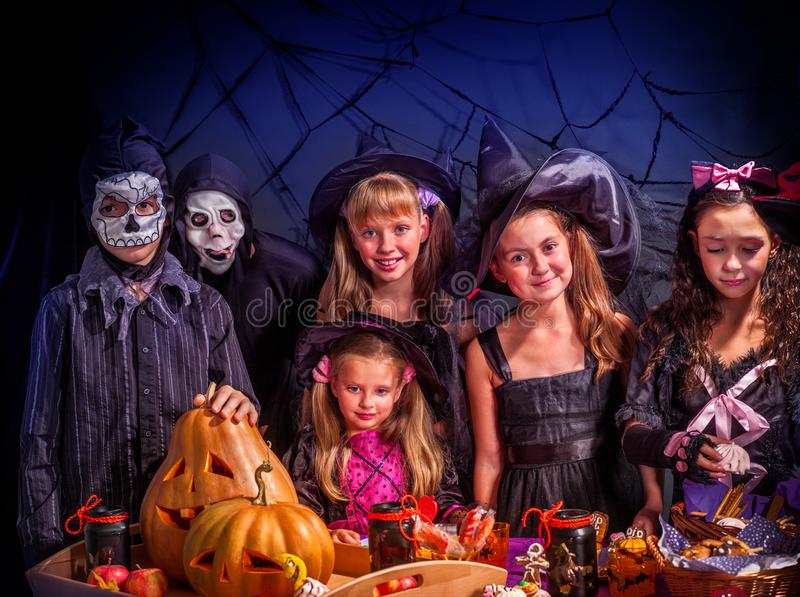 Halloween kids holding carved pumpkin . Halloween kids holding carved pumpkin as jack-o-lantern with trick or treat food at table. Black net with bat background stock images