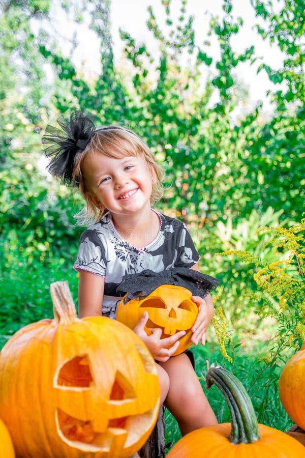 Halloween Kind kleidete im Schwarzen mit Steckfassung-Olaterne in der Hand, Süßes sonst gibt's Saures an Glücklicher Kürbis des k stockbild