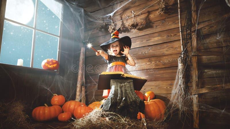 Halloween Kinderkleine Hexe mit magischem Stab und dem Ablesen eines Mag lizenzfreie stockfotos