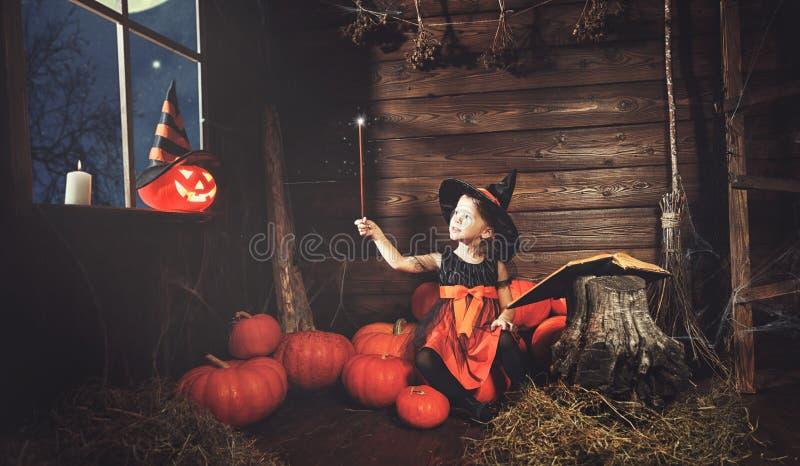 Halloween kleine Hexe beschwört mit Buch von Bannen, Magie lizenzfreies stockbild