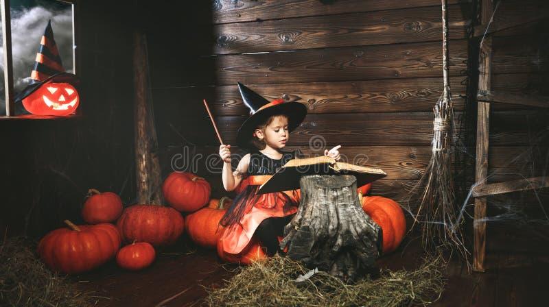 Halloween kleine Hexe beschwört mit Buch von Bannen, Weisen lizenzfreie stockfotos