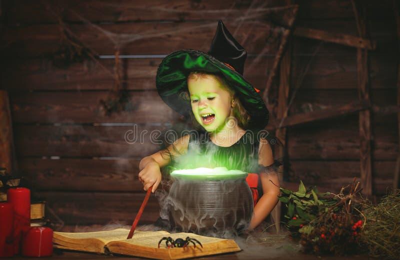 Halloween kleines Hexenkind, das Trank im Großen Kessel mit kocht lizenzfreies stockfoto