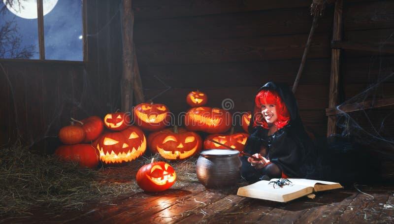 Halloween kleines Hexenkind, das Trank mit Kürbis kocht und stockfotografie