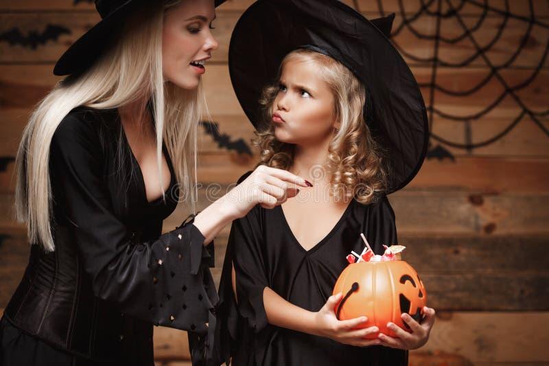 Halloween-Konzept - die schöne kaukasische Mutter, die mit ihrem wenig daugther spielt, genießen mit Halloween-Süßigkeit und -bon stockfotografie