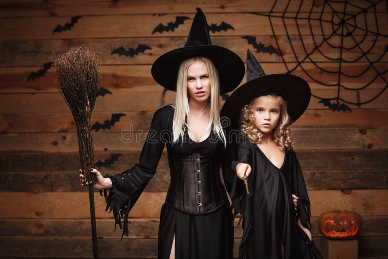 Halloween-Konzept - nette Mutter und ihre Tochter in den Hexenkostümen Halloween feiernd, das mit gebogenen Kürbisen über Schläge stockfotos