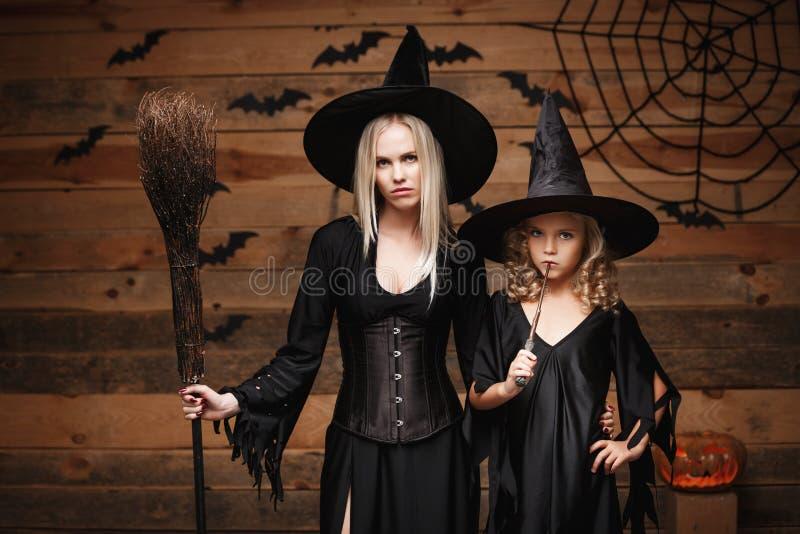 Halloween-Konzept - nette Mutter und ihre Tochter in den Hexenkostümen Halloween feiernd, das mit gebogenen Kürbisen über Schläge stockbilder