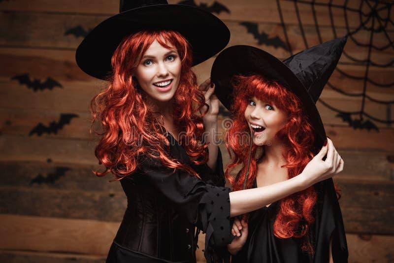 Halloween-Konzept - schöne kaukasische Mutter kleiden oben für ihre Tochter in den Hexenkostümen und in langem gelocktem Haar an, stockfoto