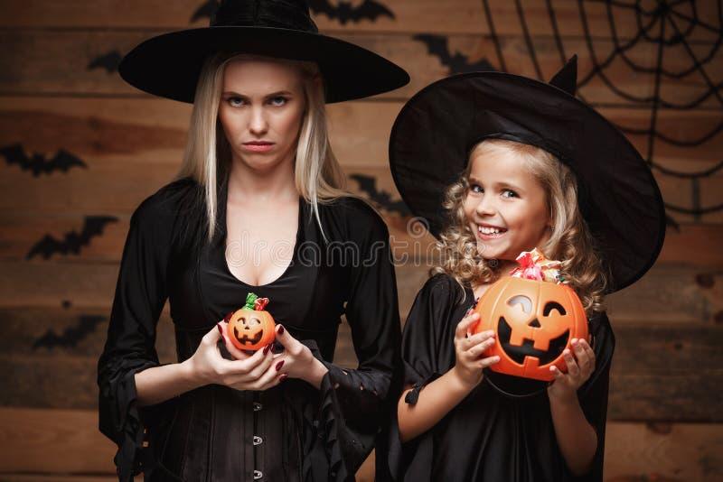Halloween-Konzept - schöne kaukasische Mutter mit enttäuschtem Gefühl mit glücklichem wenig daugther genießen mit Halloween-Süßig lizenzfreie stockfotografie