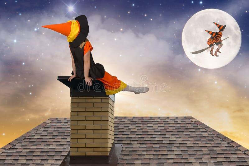 halloween Liten flicka i ett häxadräktsammanträde på taket och blick på flyget av häxor och trollkarlar i himlen royaltyfri foto