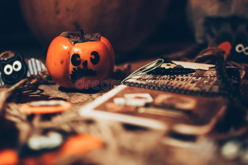Halloween little pumpkin with painted faces on a wooden floor, next to it is a notebook with bats, handmade work preparing for the stock image