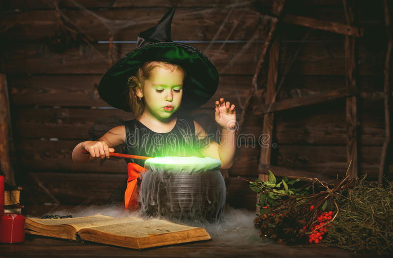 Halloween. little witch child cooking potion in cauldron with royalty free stock images