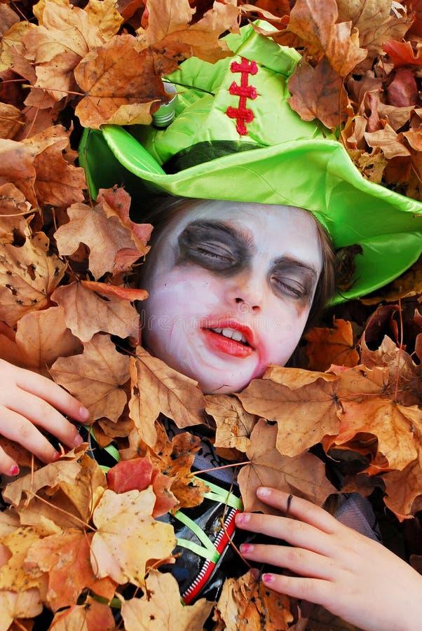 Halloween-Mädchen in den Blättern lizenzfreie stockbilder