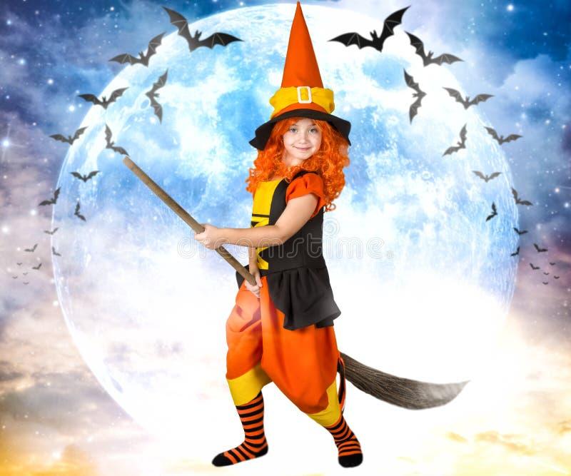 halloween Mała dziewczynka w kostiumowym czarownicy lataniu na miotle przez niebo zdjęcia royalty free