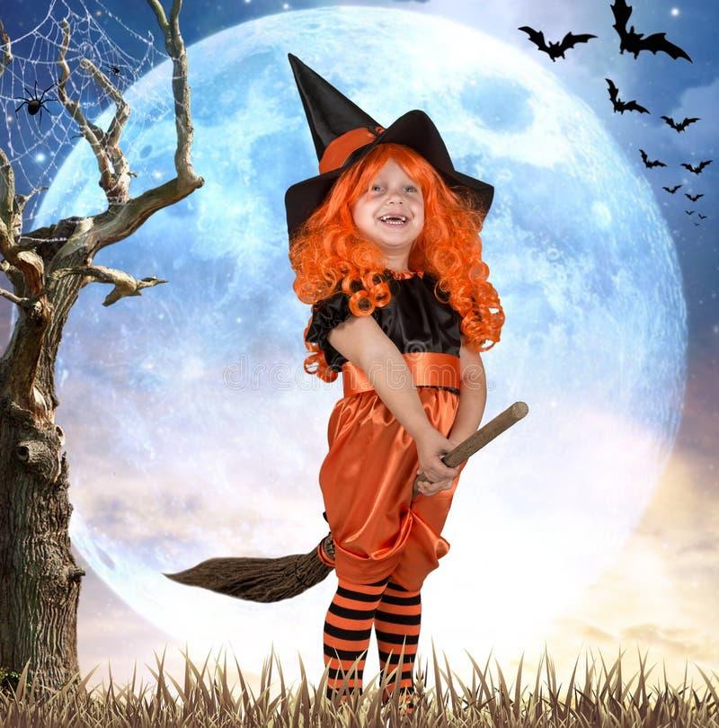 halloween Mała dziewczynka w kostiumowym czarownicy lataniu na miotle przez niebo zdjęcie stock