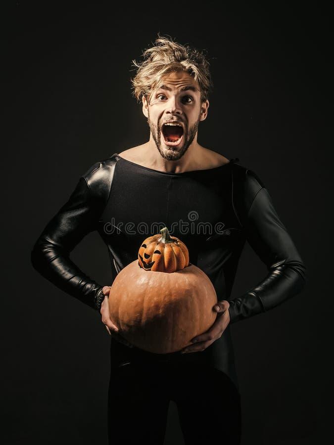 Halloween-Macho, der zwei Kürbise auf dunklem Hintergrund hält lizenzfreies stockbild
