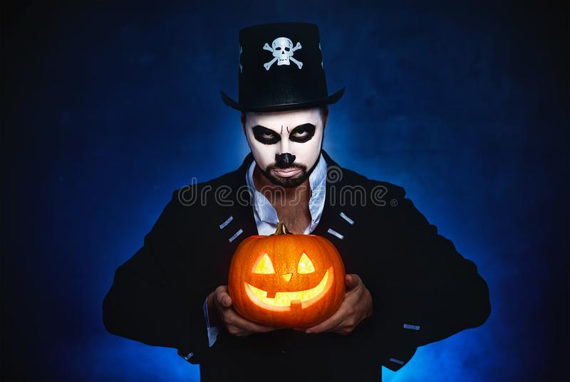 Halloween. magic skeleton with pumpkin. man in makeup and cost royalty free stock images