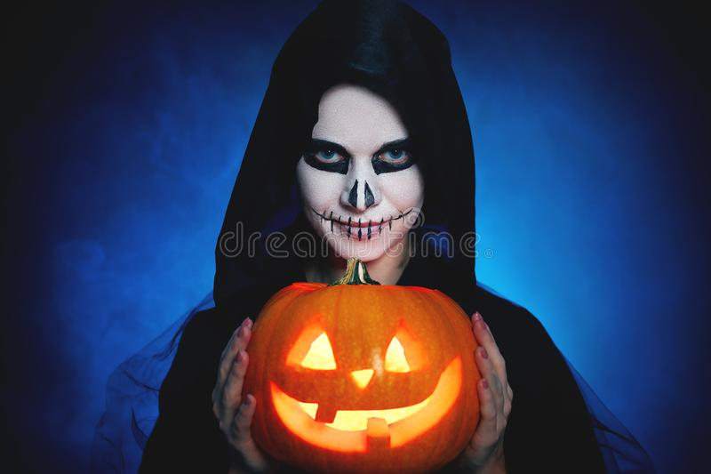 Halloween. magic skeleton with pumpkin. woman in makeup and co royalty free stock photography
