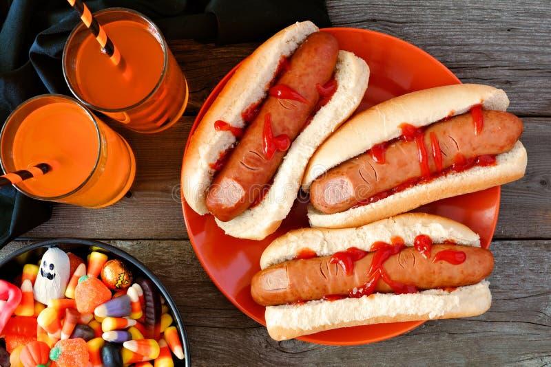 Halloween-Mahlzeitszene mit den Hotdogfingern, -getränken und -süßigkeit lizenzfreies stockfoto