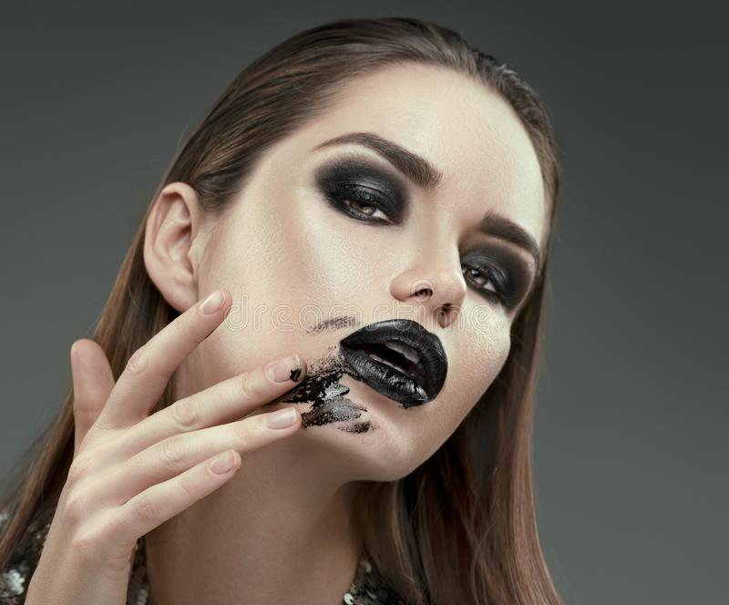 Halloween makeup. Fashion model girl with trendy gothic black make-up. Young woman smears black lipstick on her face. Closeup royalty free stock image