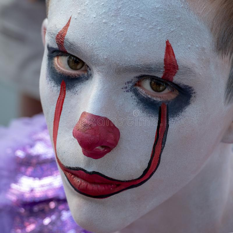 Halloween Makeup Like Pennywise. Street performer clown with a white face. The look of a man in the guise of IT on a costume royalty free stock photos