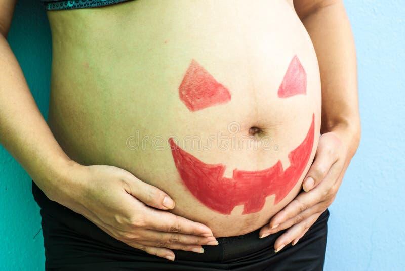 Halloween malte auf Bauch der schwangeren Frau stockfotografie