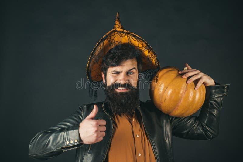 Halloween Man posing with pumpkins. Scary hipster man with beard in Halloween hat. Halloween man with pumpkin - Holidays stock image