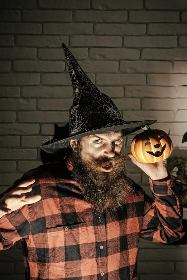 Halloween man with pumpkin in darkness. Holiday celebration symbols on brick wall. Jack o lantern. Mystery and horror concept. Hipster with frown face in witch stock photos