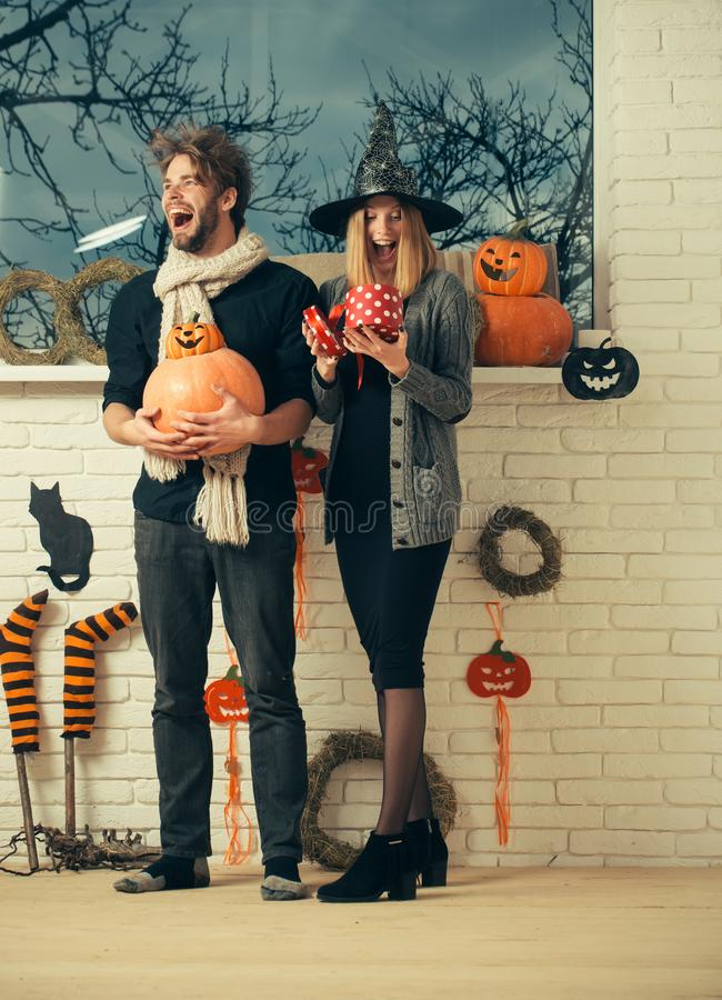Halloween man in scarf happy smiling with pumpkins. Halloween men in scarf happy smiling with pumpkins. Woman in witch hat opening gift box. Couple in love royalty free stock images