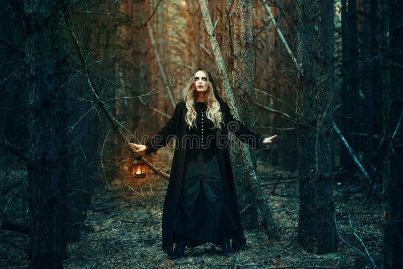 Halloween menina bonita com uma lanterna em um vestido preto na floresta fotografia de stock