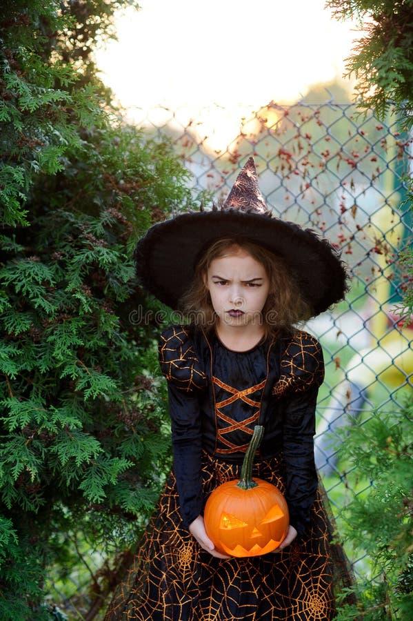 Halloween A menina de 7-8 anos representa o feiticeiro irritado imagem de stock
