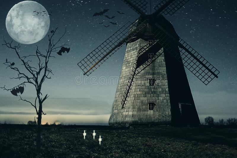 Halloween mill with Moon and bats. Old ruined sinister mill by night. Haunted mill with dark scary horror atmosphere stock photo