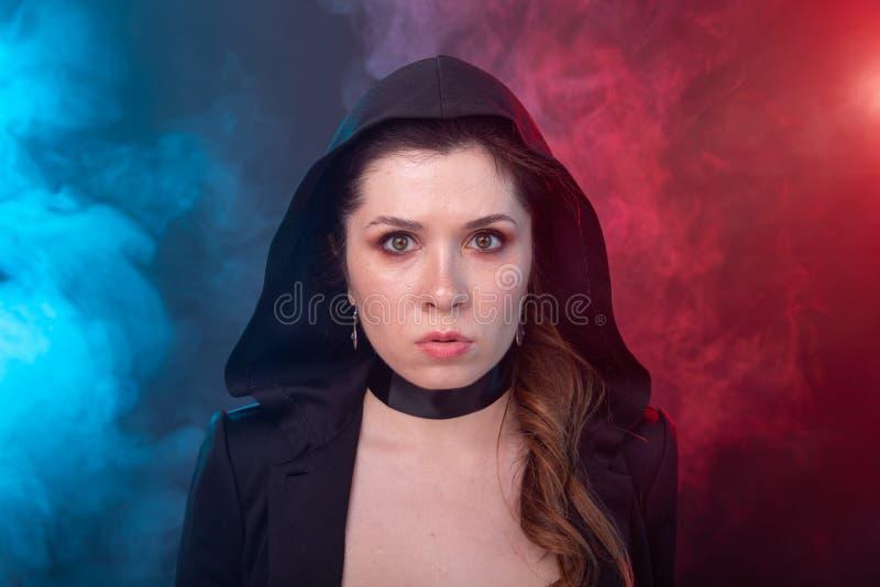 Halloween, misterioso y misterioso concepto - morena sexy mujer en capucha negra foto de archivo libre de regalías