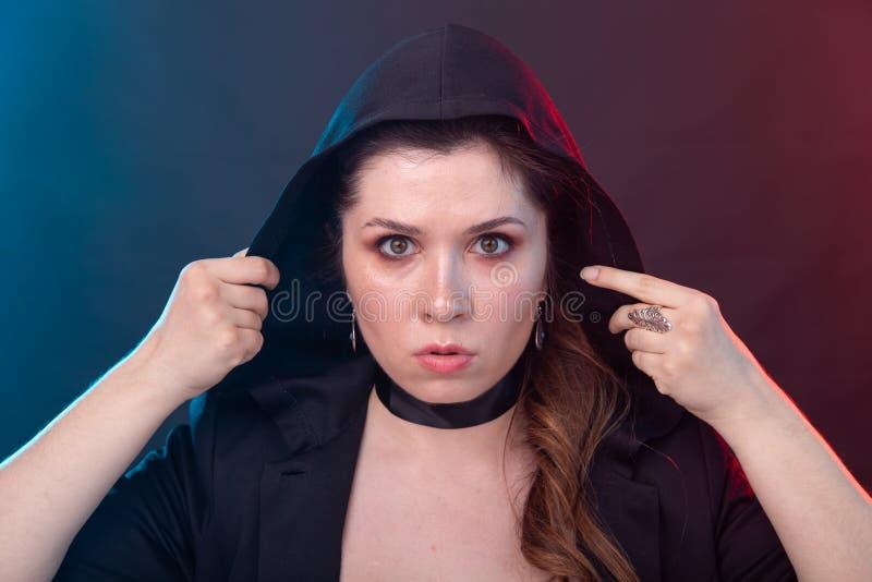 Halloween, misterioso y misterioso concepto - morena sexy mujer en capucha negra imágenes de archivo libres de regalías