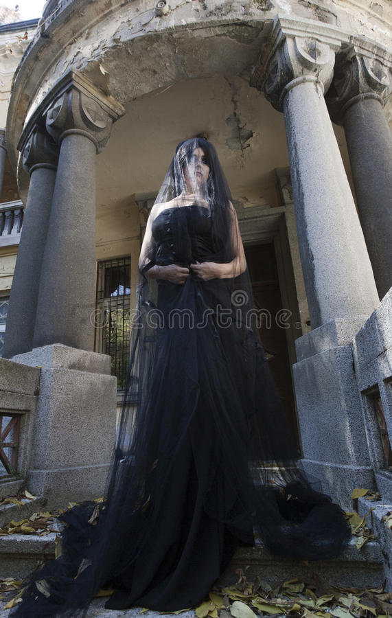 Halloween Misterious Dressed Gothic Woman. Misterious woman dressed in black gothic dress royalty free stock photo