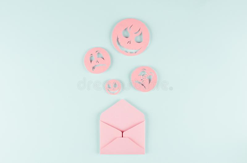 Halloween mock up with open envelope and spooky faces emoji as message of cut paper on pastel trendy blue background. royalty free stock photo