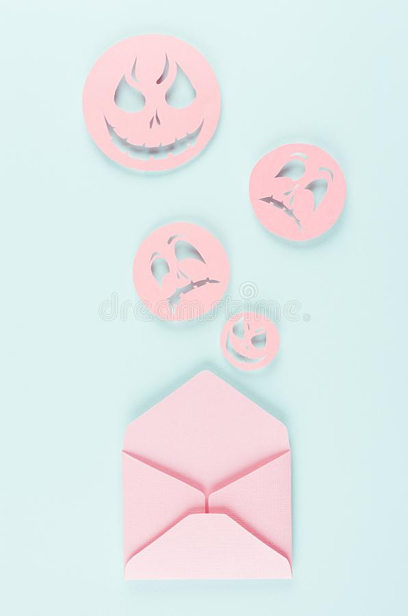 Halloween mock up with open envelope and spooky faces emoji as message of cut paper on pastel trendy mint background. Halloween mock up with open envelope and royalty free stock photography