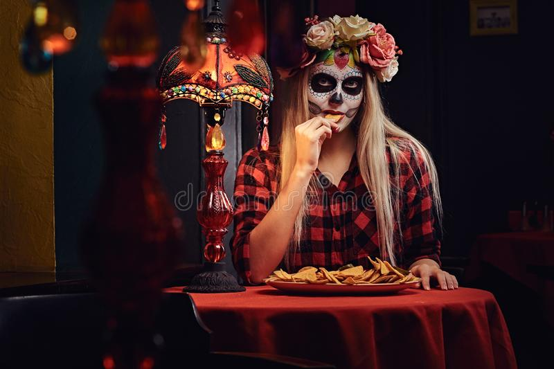 Young blonde girl with undead makeup in flower wreath eating nachos at a mexican restaurant. Halloween and Muertos concept. Young blonde girl with undead makeup stock images