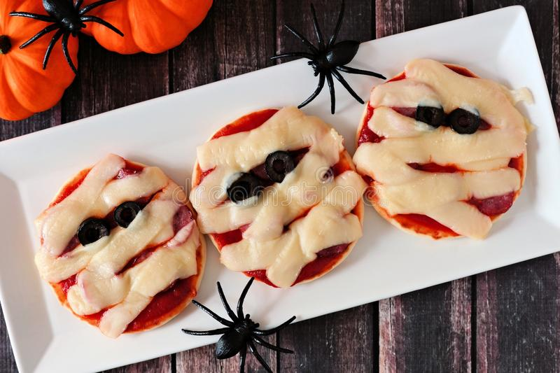 Halloween mummy mini pizzas on white plate over rustic wood. En background royalty free stock photography