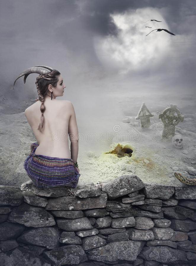 Halloween mystical background with beautiful woman on stone wall royalty free stock photography
