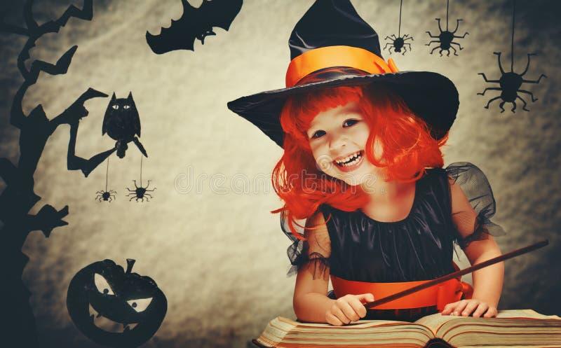 Halloween nette kleine Hexe mit magischem Stab und Buch conjur lizenzfreie stockfotos