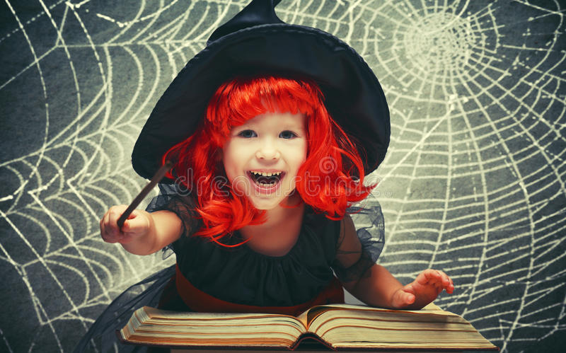 Halloween nette kleine Hexe mit magischem Stab und Buch conjur lizenzfreies stockfoto